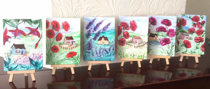 a row of cottage paintings by Hazel Rayfield